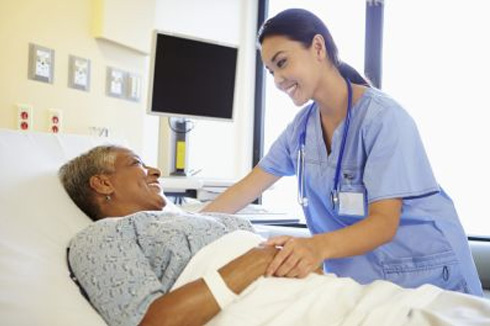 a smiling nurse at the bedside of an elderly patient